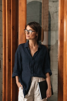 Vertical image of business woman in eyeglases with folder in hand standing near the glass door