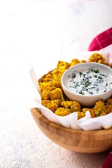 Vertical image of cauliflower with sour cream sauce in bowl on white background. dietary garnish concept
