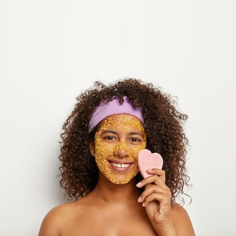 L'immagine verticale di una donna allegra e felice applica uno scrub al sale marino per assorbire lo sporco e pulire i punti scuri sul viso, mantiene una buona idratazione, tiene la spugna a forma di cuore vicino alla guancia, inverte le cellule della pelle