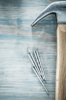Vertical image of claw hammer nails on wooden board construction concept