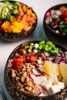 魚、米、新鮮な野菜とポケボウルの垂直方向の画像のクローズアップ