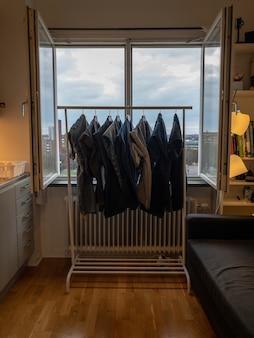 L'immagine verticale di vestiti ad asciugare su una rastrelliera metallica contro una finestra aperta