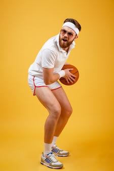 Immagine verticale di sportivo concentrato in occhiali da sole giocando a basket