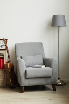 Vertical image of cozy grey armchair next to white wall in male design interior
