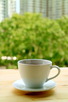 Vertical image of a cup of hot tea on the window side wooden table