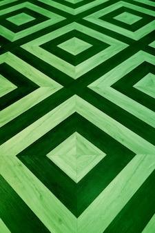 Vertical image of dark and light green geometric pattern wooden floor
