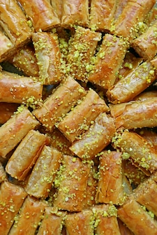 Vertical image of delectable baklava pastries topped with chopped pistachio nuts