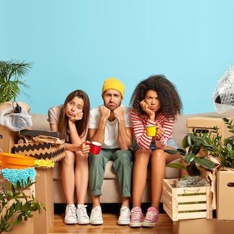 L'immagine verticale di tre amici multietnici insoddisfatti si trasferisce in un altro luogo, fa una pausa caffè dopo aver disimballato gli effetti personali, guarda con insoddisfazione, si siede sul divano contro il muro blu nel soggiorno