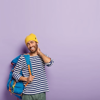 Vertical image of fatigue european man touches neck, suffers from pain in neck, dressed in casual wear, carries backpack on shoulder, smirks face, shows white teeth, isolated over purple background