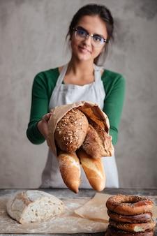 Immagine verticale del panettiere femminile che mostra borsa con pane