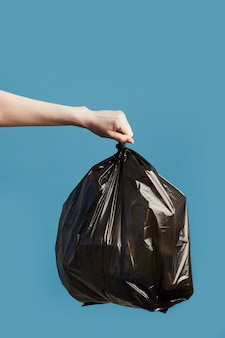 Vertical image of female hand holding black trash bag, waste sorting and recycling concept
