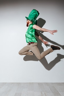 Vertical image of flying man in st.patriks costume