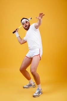 Immagine verticale dello sportivo divertente che gioca a tennis