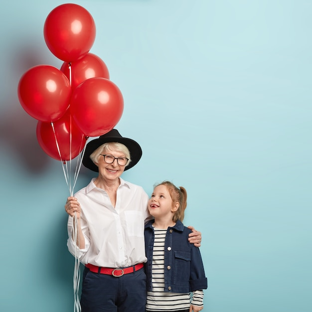 Vertical image of glad granny and small female child embrace, have nice relationships, celebrate holiday together, holds red balloons, enjoy birthday party, isolated on blue. family portrait.