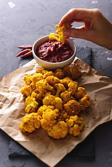 Vertical image hand waving fried cauliflower in tomato sauce on parchment paper on grey background. vegetarian snack concept