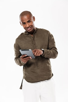 Vertical image of happy african man using tablet computer and looking
