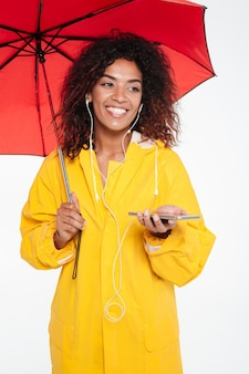 Vertical image of happy african woman in raincoat hiding under umbrella and listening music on her phone while looking away over white