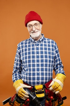 Vertical image of happy experienced elderly male builder with gray beard posing at blank wall, wearing glasses, rubber gloves, hat and belt with instruments, looking  with broad smile