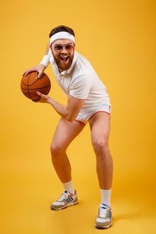 Immagine verticale di sportivo felice in occhiali da sole giocando a basket
