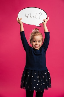 Vertical image of happy young blonde girl holding speech bubble what and looking at the camera over pink wall