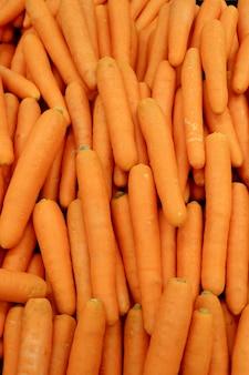 Vertical image of heap of vibrant orange color fresh carrots for background