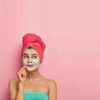 L'immagine verticale di una donna adorabile con un'espressione pensierosa, tiene il dito vicino all'angolo delle labbra, guarda sopra, applica una maschera facciale per rinfrescarsi, avvolto in un asciugamano morbido.