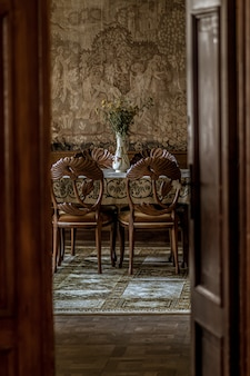 Vertical image of a luxurious dining room with ornate chairs as seen through an open door
