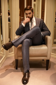 Vertical image of man sitting on armchair
