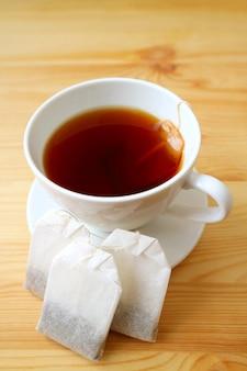 木製のテーブルにティーバッグと熱いお茶のカップの垂直方向の画像
