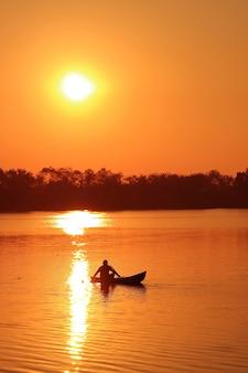 午後遅くに湖でボートに取り組んでいる漁師のシルエットの垂直方向の画像