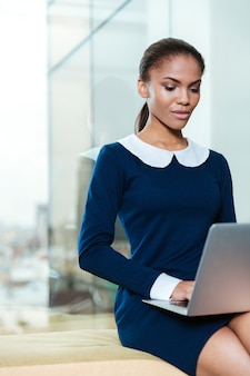 ラップトップコンピューターで窓の近くに座っているドレスを着たアフロビジネス女性の垂直方向の画像
