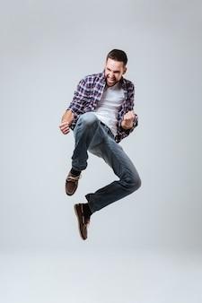Вертикальное изображение бородатого мужчины в рубашке, который прыгает