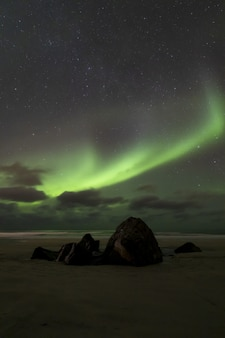 星空を背景にした大西洋の息を呑むようなオーロラ現象の垂直方向の画像