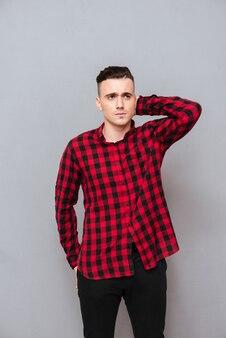 Вертикальное изображение недовольного молодого человека в рубашке и черных джинсах. изолированный серый фон