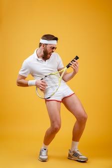 Вертикальное изображение забавного спортсмена, играющего на теннисной ракетке