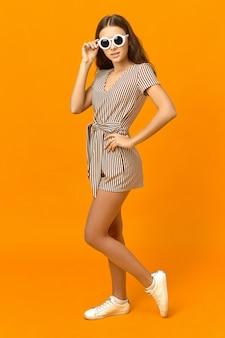 Вертикальное изображение великолепной модной молодой девушки-модели со стройным телом, позирующей в оранжевой студии