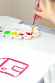 Вертикальное изображение руки девушки рисунок дома на белой бумаге с красной акварелью. время рисования.