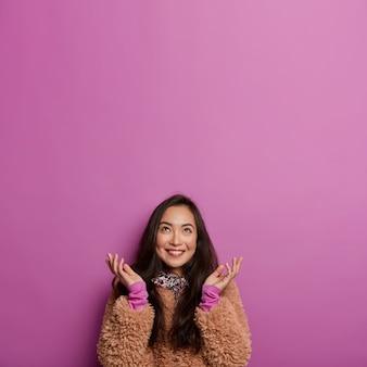 幸せなアジアの女性の垂直方向の画像は、うまくいけば上に見え、手のひらを横に広げ、優しい笑顔を持ち、冬のコートを着ています