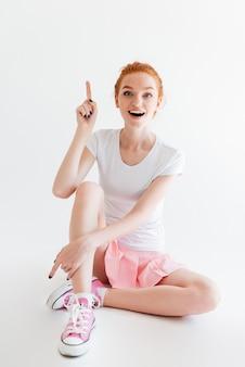 Вертикальное изображение счастливой девушки имбиря имея идею и смотря