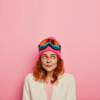 スノーボードウェアで幸せな物思いにふける女性旅行者の垂直方向の画像は、バラ色の壁の上に隔離され、上に焦点を当てた赤い髪をしています。