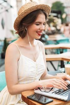 ドレスと麦わら帽子の幸せな女性の垂直方向の画像