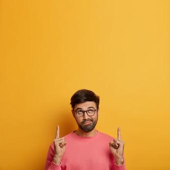 호기심이 많은 수염 난 남자의 수직 이미지는 위의 앞쪽 손가락을 가리키고 입술을 지갑에 넣고 흥미로운 것을 보여주고 노란색 벽에 고립 된 장밋빛 점퍼를 입고 제품을 보여줍니다. 이 방향을 따르십시오