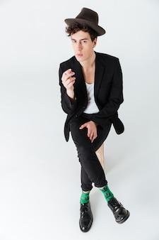 Вертикальное изображение человека в костюме сидит и курит сигарету