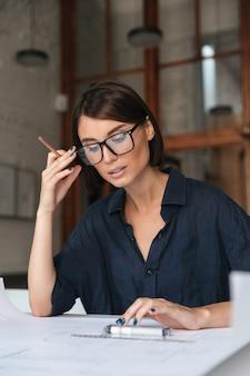 Вертикальное изображение задумчивой бизнес-леди в очках