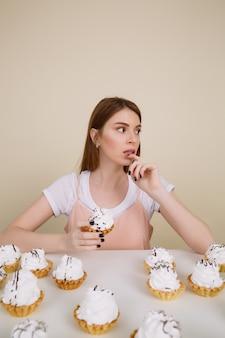ケーキとテーブルで物思いにふける女性の垂直方向の画像