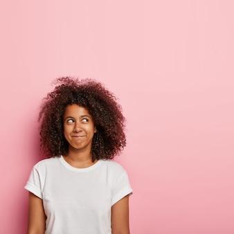 かなり夢のような若い女性の垂直方向の画像は、唇を押し続け、幸せに満ちた目で上に焦点を合わせ、何か楽しいものを想像し、ボリュームのある濃いカリカリの髪を持ち、カジュアルな白いtシャツを着ています。
