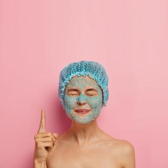 Вертикальное изображение довольной красоты: девушка имеет скраб на лице с синей морской солью, закрывает глаза и указывает указательным пальцем вверх, носит банный колпак, проводит выходные в спа-салоне, имеет проблемную сухую кожу, режим красоты