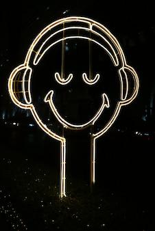밤에 길가에 행복 한 얼굴 모양의 네온 빛 기호 미소의 세로 이미지