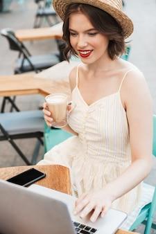 ドレスと麦わら帽子の笑顔の女性の垂直方向の画像