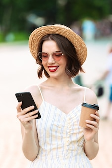 Вертикальное изображение улыбающейся женщины в платье, соломенной шляпе и солнцезащитных очках, пьющей кофе и использующей смартфон на открытом воздухе